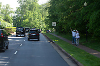 Pedestrians wave at the presidential motorcade carrying United States President Donald J. Trump as he he travels to Trump National Golf Club in Sterling, Virginia on Saturday, May 23, 2020.  Credit: Stefani Reynolds / CNP/AdMedia