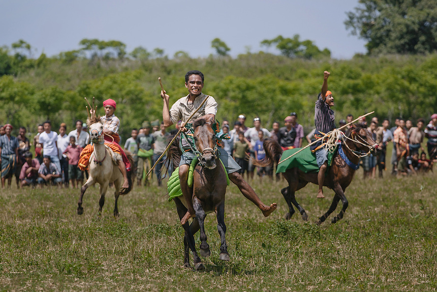 Three Pasola warriors ready to charge the enemy forces during the event in Wainyapu, Kodi. Pasola is an ancient tradition from the Indonesian island of Sumba. Categorized as both extreme traditional sport and ritual, Pasola is an annual mock horse warfare performed in response to the harvesting season. In the battelfield, the Pasola warriors use blunt spears as their weapon. However, fatal accident still do occurs.