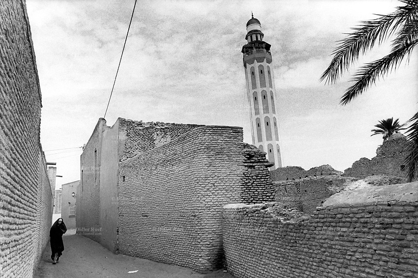 Tunisia. Tozeur Governorate. Tozeur. A lonely muslim woman walks in the medina (old city) on a sandy alley in between houses near the local mosque. She wears the abaya and the hidjab (islamic headscarf) on her head to cover their hair. The abaya, sometimes also called aba, is a simple, loose over-garment, essentially a robe-like dress, worn by some women in parts of the Islamic world. Traditional abaya are black and may be either a large square of fabric draped from the shoulders or head or a long caftan. The abaya covers the whole body except the face, feet, and hands. The word hijab (or hidjab) refers to both the veil covering the head and traditionally worn by muslim women (Islamic headscarf), but also the  modest muslim styles of dress in general. Tozeur is an oasis and a city in south west Tunisia. 15.09.94 © 1994 Didier Ruef