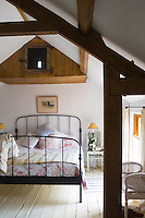 A cosy yet fresh and bright bedroom is located under the eaves