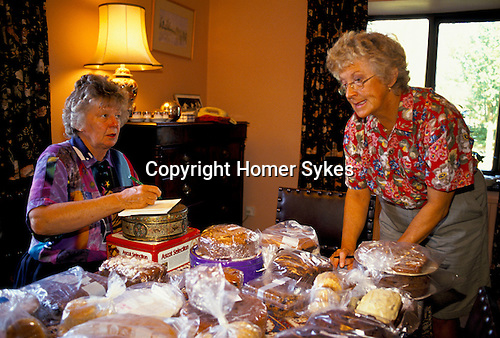 'ENGLISH VILLAGE FETE', TWO LADIES FROM THE VILLAGE FETE ORGANISING COMMITTEE, PRICING CAKES AND JARS OF JAM MADE BY VILLAGERS FOR THE AUGUST SUMMER FETE.