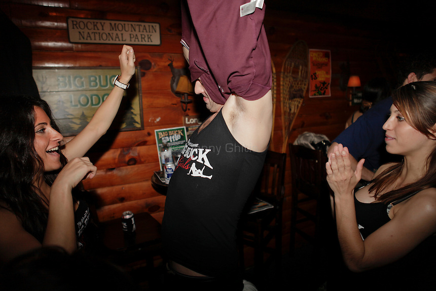 Big Buck Girls Andrea Miele, 23, left, and Alicia Patterson, 24, right, cheer as Sam Jaffe, 27, changes into a Big Buck Girl shirt at The Black Bear Lodge in Manhattan, which hosted an official Big Buck Party on Thursday April, 28, 2011. Fans of the popular hunting arcade game were invited to test their skill against other Big Buck Hunter fans to compete for prizes, enter to win raffle merchandise and meet Big Buck Girls...Danny Ghitis for The New York Times
