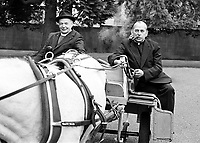 Roman Catholic Cardinal Tomas O Fiach smoking his pipe alongside Church of Ireland Primate John Armstrong in an Irish jaunting car at a Tourist Board function to publicise the City of Armagh, N Ireland, UK. The two church leaders were close friends. Armagh is the Irish ecclesiatical captial for both denominations. 198005001. <br />