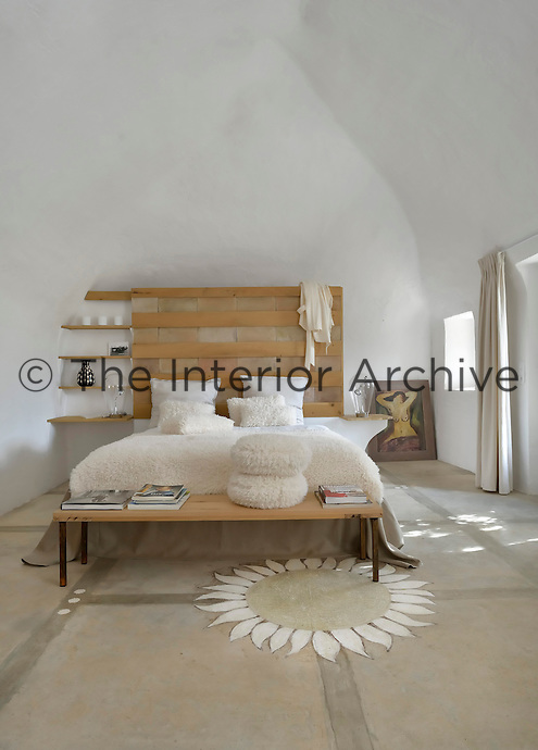 The bedroom features a double bed with a headboard of natural oak and the concrete floor is decorated with a sunflower motif