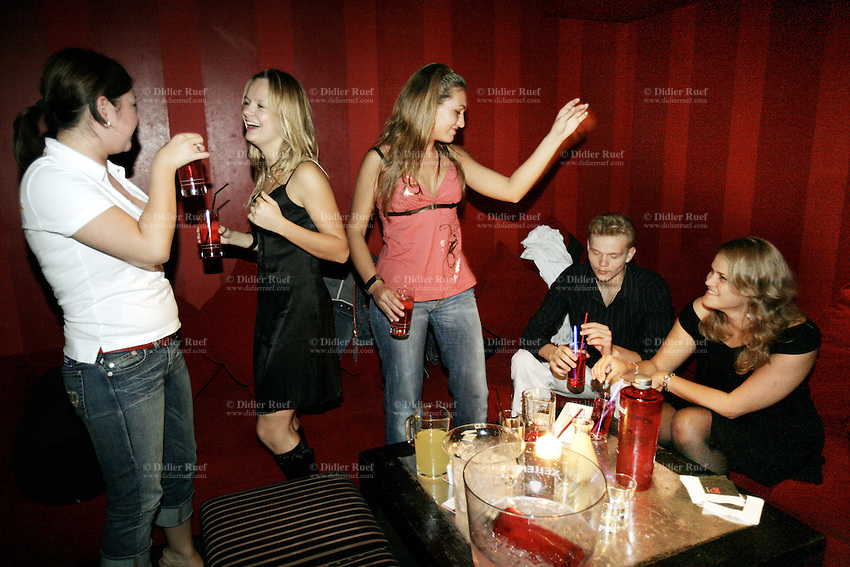 Switzerland. Canton Vaud. Lausanne. Red club. Exclusive and VIP party for the lauch of Xellent Vodka, the first and only Swiss Vodka. A group of young girls and a boy have an alcoholic drink on a table. Night life. © 2006 Didier Ruef