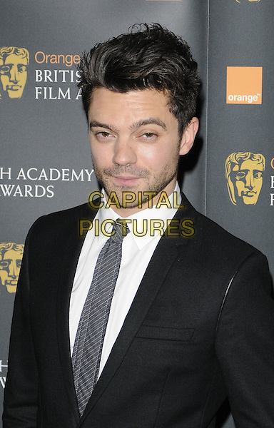 DOMINIC COOPER.The nominations for The Orange British Academy Film Awards (BAFTAs) at BAFTA headquarters, London, England..January 18th, 2011.headshot portrait black grey gray suit white shirt stubble facial hair half length .CAP/CAN.©Can Nguyen/Capital Pictures.