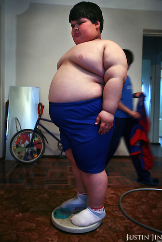 Dzhambulat Khotokhov, 6, one of the fattest boys in the world, weighs himself at home in Terek, in southern Russia. .Now 1.4 metres tall and weighing about 100 kg, Khotokhov has grabbed world attention as the biggest kid in the world since he was three. .Khotokhov lives with his mother Neyla and his brother, 14-year-old Mukha. .