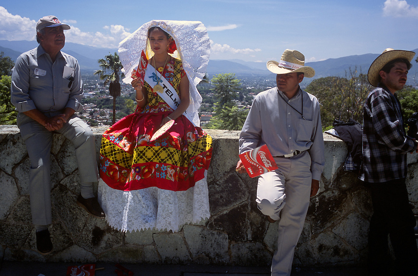 A traditionally-dressed usher takes a break on a wall outside the city amphitheater during the Guelaguetza dance festival in Oaxaca, Mexico.