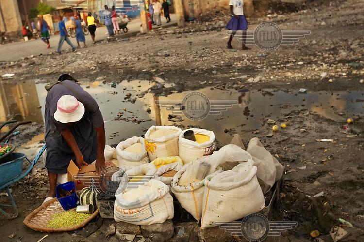 A woman sells grain. Recent price rises caused food riots in the Cite Soleil slum.