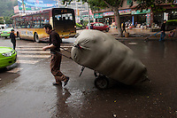 Daytime landscape view of a man pulling a hand cart loaded with a large burlap bag on Hui Long Jie in Lóngmǎtán Qū of the Lúzhōu Prefecture City in Sichuan Province.  © LAN