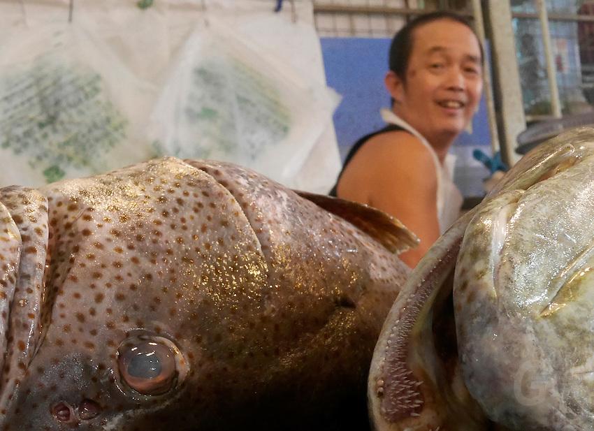 Fish vendor and the eyes of the fish, Phnom Penh market, Cambodia