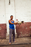 PHILIPPINES, Manila, portrait of a man with his cock fighting rooster in the Intramros District on Beatero Street