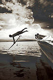INDONESIA, Mentawai Islands, Kandui Surf Resort, surfer diving into the Indian Ocean with his surfboard (B&W)