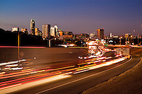 Sunset falls on the Austin Skyline as I-35 Rush Hour Traffic flows through downtown Austin, Texas.