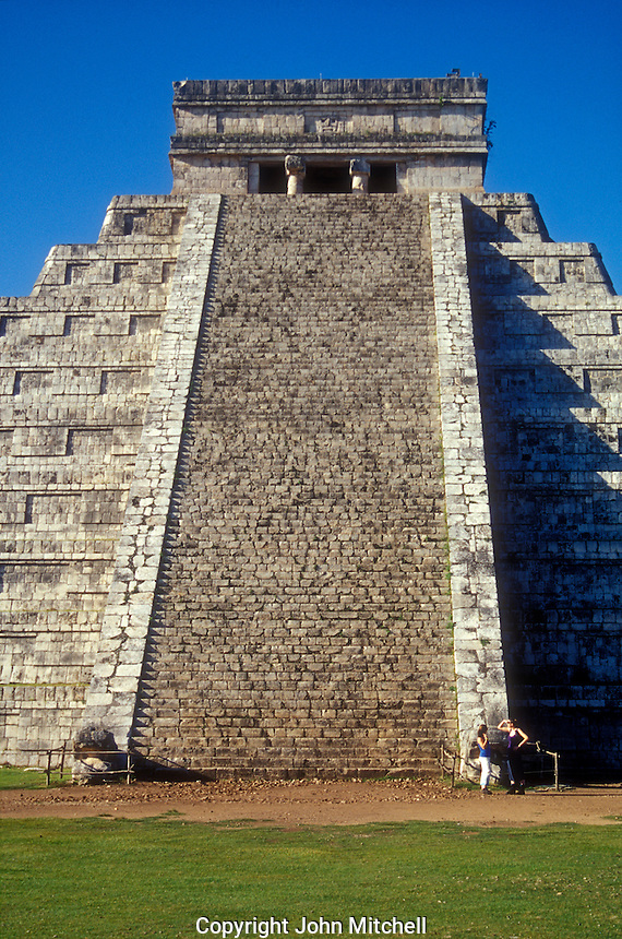 Tourists standing in front of El Castillo or Pyramid of Kukulcan at the Mayan ruins of Chichen Itza, Yucatan, Mexico