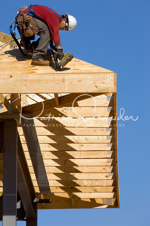 02/22/07:  A construction worker attaches plywood sheets to create a new roof during expansion/construction of a Charlotte-area shopping center. Charlotte, NC, is one of the country's fastest-growing cities. ..By Patrick Schneider- Patrick Schneider Photography.