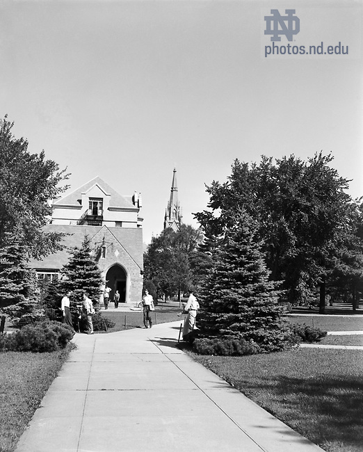 GPHR 45/0050:  Male students walking on South Quad with the Post Office (now the Knights of Columbus Building), Walsh Hall, and Basilica of the Sacred Heart in the background, c1950s..Image from the University of Notre Dame Archives.