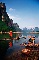 Landscape image of Li River Cormorant fishermen on bamboo rafts in the Karst Hills. Guilin Guangxi, China.