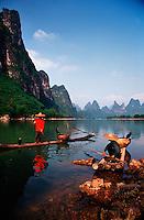 Landscape image of Li River Cormorant fishermen on bamboo rafts in the Karst Hills. Guilin Guangxi, China.