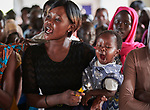 As her baby yawns, a woman sings during Catholic Mass in Bunj, the host community for the Doro Refugee Camp in Maban County, South Sudan. Doro is one of four camps in Maban that together shelter more than 130,000 refugees from the Blue Nile region of Sudan. Jesuit Refugee Service provides educational and psycho-social services to both refugees and the host community. <br /> <br /> Misean Cara supports the work of JRS in the Maban camps and host community.