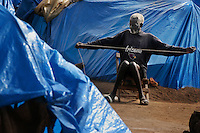 Agole John, 75,  creates rope to create a sleeping mat while living in Lira Cultural Center Camp for internally displaced persons. He arrived in march of 2003 after a close call with rebels. They campe to his home, slaughtered his goats and chickens for supper and then slept. In the morning the group left, leaving him alive. Given the reprieve, he realized how dangerous it was in his village and immediately fled.  (Rick D'Elia) April 2004.