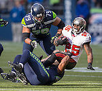 Seattle Seahawks  defensive tackle Chris Clemons (91) wraps up Tampa Bay Buccaneers running back Mike James (25) n the second quarter at CenturyLink Field in Seattle, Washington on  November 3, 2013.  The Seahawks beat the Buccaneers 27-24 in overtime.  ©2013. Jim Bryant. All Rights Reserved.
