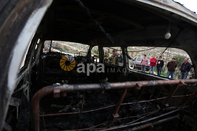 Palestinians and Israeli soldiers inspect a burnt vehicle following an apparent price tag attack by Jewish settlers in the West Bank village of Deir Jarir, northeast of Ramallah, on February 5, 2013. Suspected Jewish extremists torched a vehicle and scrawled Hebrew graffiti on a nearby wall in the village, Palestinians and Israelis said. Photo by Issam Rimawi