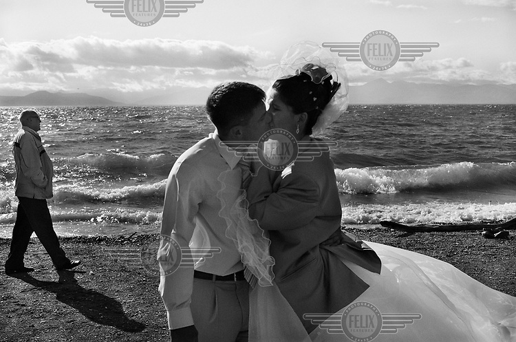 A young couple stand by the shore and kiss on their wedding day near the city of Petropavlovsk Kamchatsky in Kamchatka region.