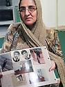 Iran 2004  Une Kurde de Sardasht , victime des armes chimiques utilis&eacute;es par les Irakiens  pendant la guerre Iran-Irak, montrant des photos de membres de sa famille morts suite aux bombardements.<br /> Iran 2004  A Kurdish woman from Sardasht, victim of chemical weapons , after the bombing of her city by the Iraqis, shows photos of her dead relatives because of the bombing<br /> ئیران 2004 , ئه و کورده خه لکی سه رده شته , له گه ل بنه ماله که ی تووشی بومبارانی کیمیاوی بووه که عییراقییه کان له کاتی شه ری  ئیران  و  عیراق به کارییان هیناوه. لیره , وینه ی ئه ندامانی بنه ماله که ی که له بومبارانی کیمیاوی کوژراون , نیشان ده دات