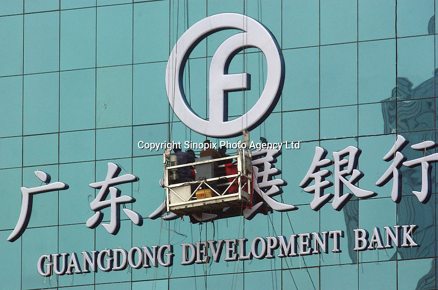 Workers put up a sign for Guangdong Development Bank in Beijing, China. .