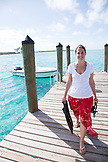 EXUMA, Bahamas. Nicole, one of the managers of the Fowl Cay Resort standing at the dock holding masks and fins for snorkeling.