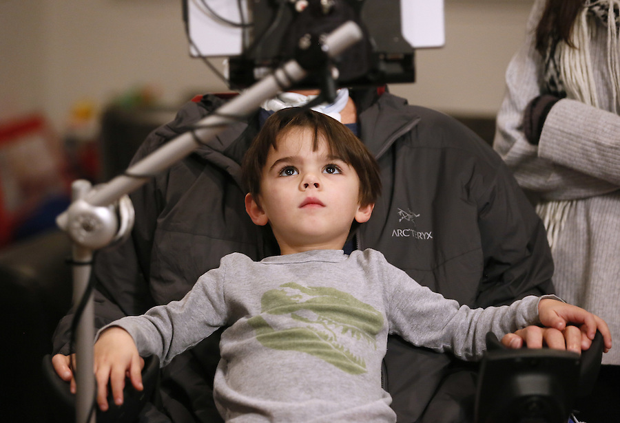 "In this Monday, Jan. 18, 2016 photo, former New Orleans Saints NFL football player Steve Gleason's 4-year-old son, Rivers, sits on his father's lap during an interview in New Orleans. ""GLEASON,"" a feature-length documentary that gives an unfiltered look at his life with ALS premieres at the Sundance Film Festival on Saturday. (AP Photo/Jonathan Bachman)"