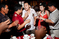 During a wedding reception, held at the West Lake Restaurant for Zhuang Tianzhu (bridegroom) and Liu Huan (bride), Zhuang breathes Baijiu, a strong grain spirit, fumes at his friend to prove that he has drunk a full glass. The groom has to make a toast at each table and his friends playfully accuse him of not emptying the whole glass. The wedding party is one of four being held at The West Lake Restaurant on the same night. Able to seat up to 5,000 people at one sitting, The West Lake Restaurant is the biggest Chinese restaurant in the world. Each week its diners, who staff are taught are 'the bringers of good fortune', devour 700 chickens, 200 snakes, 1,200 kgs of pork and 1,000 kgs of chillis. Its 300 chefs cook in five kitchens and its staff total more than 1,000.It is fully booked most nights.