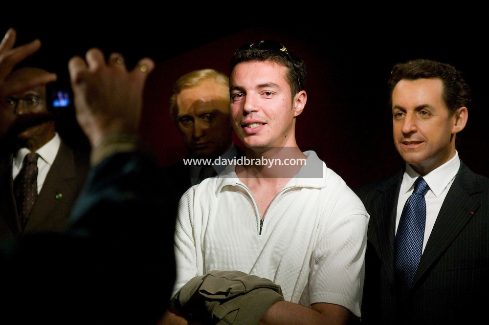 A visitor to the Grevin museum in Paris, France, poses for photographs with the wax statue of Nicolas Sarkozy, French President-elect, 15 May 2007.