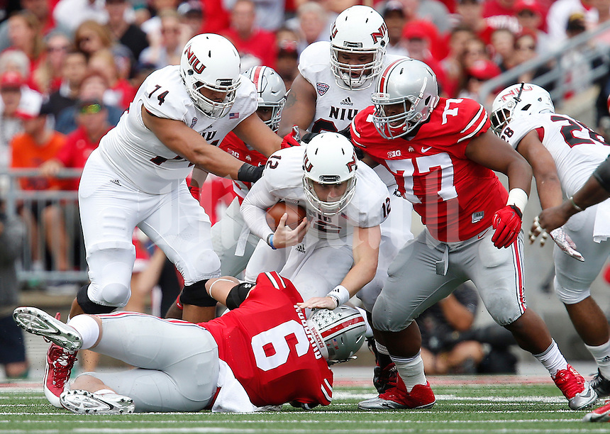 Ohio State Buckeyes defensive end Sam Hubbard (6) and Ohio State Buckeyes defensive lineman Michael Hill (77) take down Northern Illinois Huskies quarterback Drew Hare (12) on a third down in the second quarter of the college football game between the Ohio State Buckeyes and the Northern Illinois Huskies at Ohio Stadium in Columbus, Saturday afternoon, September 19, 2015. As of half time the Ohio State Buckeyes were tied with the Northern Illinois Huskies 10 - 10. (The Columbus Dispatch / Eamon Queeney)