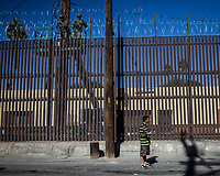 "MEXICALI,  MEXICO - November 26. A street candy sellar walks the street while US army soldiers work  fortifying the US-Mexico border fence with barbed wireon November 26, 2018 in Mexicali, Mexico.<br /> The U.S. government said it was starting work to ""harden"" the border crossing  Mexico, to prepare for the arrival of a migrant caravan leapfrogging its way across western Mexico. For the Trump administration and those who support the president's hard-line stance on illegal immigration, the chaos illustrated what they long have feared. For others, the images of the Border Patrol using tear gas on a group of migrants that included children were deeply disturbing (Photo by Luis Boza/VIEWpress)"