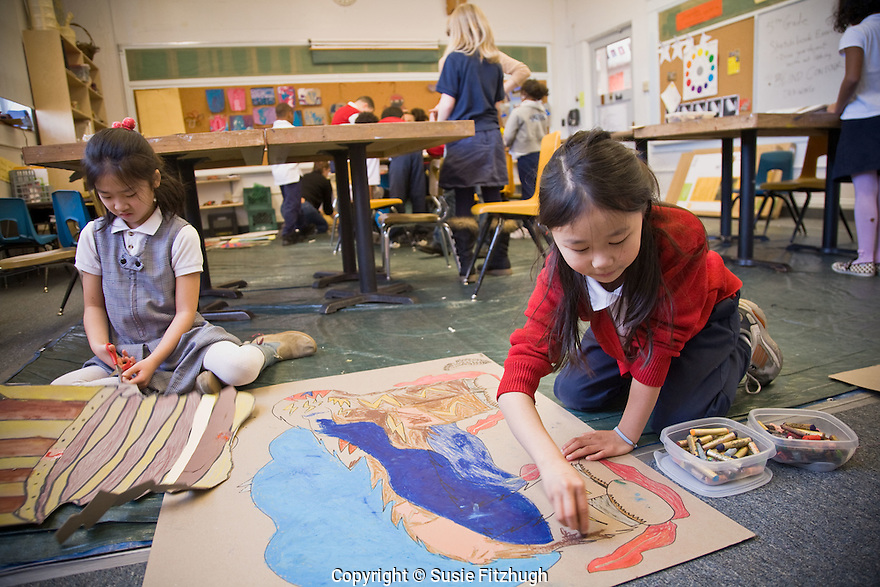 On the floor in Lauren Atkinson's Arts Corps class at St. Therese School, girls work on their projects.