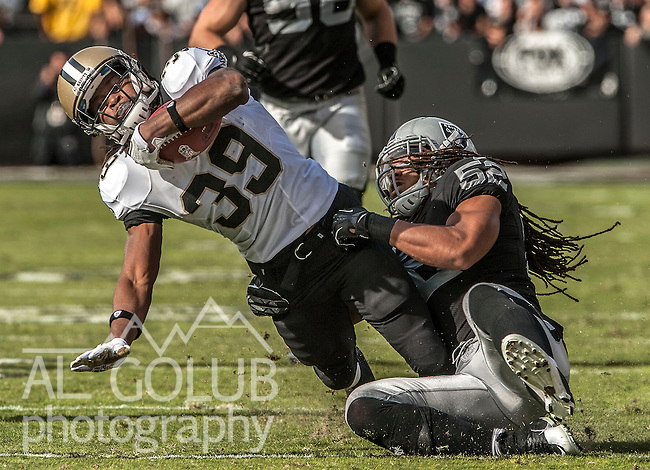 Oakland Raiders outside linebacker Philip Wheeler (52) tackles New Orleans Saints running back Travaris Cadet (39) on Sunday at O.co Coliseum in Oakland, CA.  The Saints defeated the Raiders 38-17...