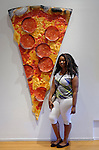 "Roslyn Harbor, New York, USA. August 24, 2016. JESSICA, of Long Island, poses next to artwork ""Pizza"" by artist Peter Anton (b. 1963, American) mixed media, of slice of Pizza with pepperoni slices, at Feast for the Eyes exhibition focusing on food and dining in art, by artists of 2D and 3D artwork, at Nassau County Museum of Art in Long Island."