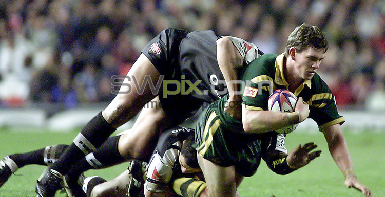Picture by Shaun Flannery\SWpix.com - 25/11/00 - Rugby League World Cup Final 2000 - Australia v New Zealand, Old Trafford, Manchester, England - Australia's Matthew Gidley is brought down by the New Zealand defence.
