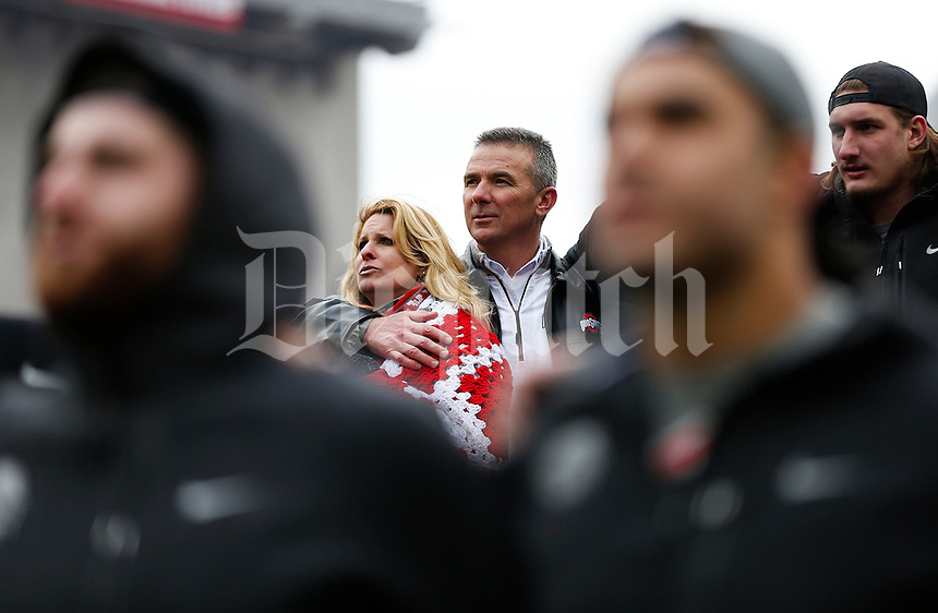 Head coach Urban Meyer holds his wife Shelley as the team sings Carmen Ohio during the Ohio State Football National Championship Celebration at Ohio Stadium, Saturday morning, January 24, 2015. More than 40 thousand fans packed the lower stands in the stadium to celebrate the National Championship win with the football team. (The Columbus Dispatch / Eamon Queeney)