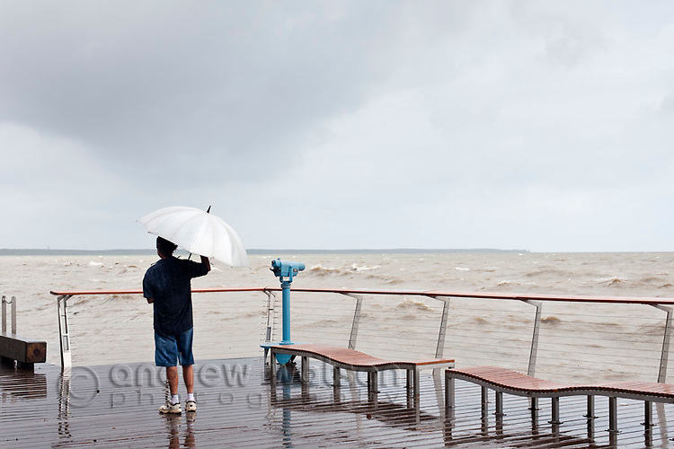 A man stands on the Esplanade boardwalk during stormy weather.  Cairns, Queensland, Australia