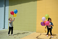 Roman Smolinski, 3, (left) and his twin sister, Charleston Smolinski, both of Rogers, hold balloons Thursday, May 21, 2020, while taking family photographs in front of the Maude Wall at Maude Boutique in Fayetteville. The clothing store invites patrons to use their multicolored back wall for photographs. Visit nwaonline.com/200522Daily/ for today's photo gallery.<br /> (NWA Democrat-Gazette/Andy Shupe)