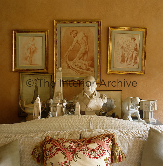 A collection of sepia engravings match perfectly the colour with which John Fowler has painted the walls of the intimate living room