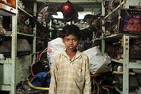 A young boy stands outside his family's store in the Chandhi Chowk electronics market in Kolkata, India. November, 2013
