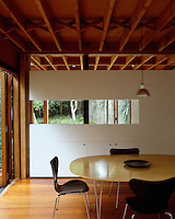 The interplay between the wooden frame and solid walls gives a boat-house feel to the dining room