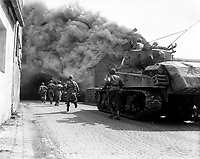 Soldiers of the 55th Armored Infantry Battalion and tank of the 22nd Tank Battalion, move through smoke filled street.  Wernberg, Germany.  April 22, 1945.  Pvt. Joseph Scrippens.  (Army)<br /> NARA FILE #:  111-SC-205298<br /> WAR & CONFLICT BOOK #:  1094