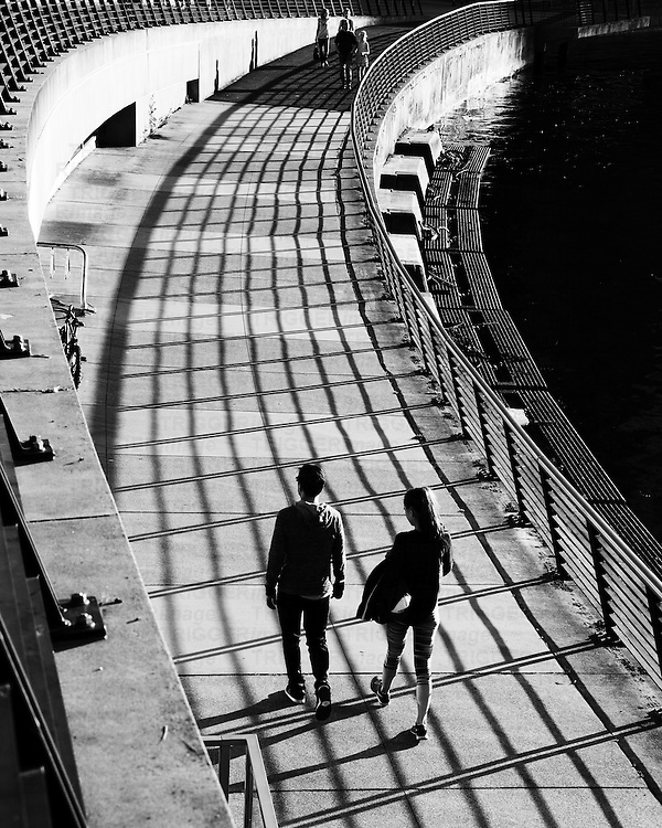 People walking in shadows of squares, with curved fence.