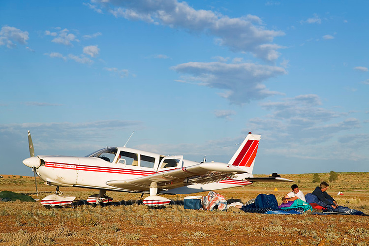 Campers sleep next to their planes at the Birdsville aerodrome during the annual Birdsville Races.  Every September hundreds of aircraft arrive at the remote town in southwest Queensland for the most famous horse racing carnival in outback Australia.  Birdsville, Queensland, AUSTRALIA.