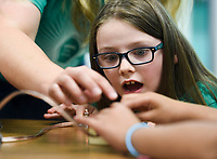 NWA Democrat-Gazette/CHARLIE KAIJO Addison Garrett reacts as a fellow student uses a lighting device to demonstrate kinetic and potential energy during a STEM summer camp, Monday, June 10, 2019 at Bonnie Grimes Elementary School in Rogers.<br />